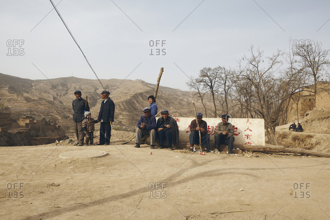 Gansu Province, China - March 21, 2013: Group of men resting in the Gansu Province, China