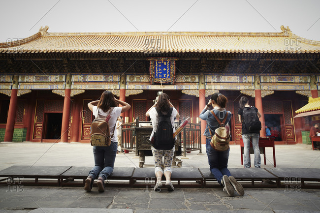 Beijing, China - September 16, 2013: Girls kneeling in front of the Yonghegong Temple, Beijing, China