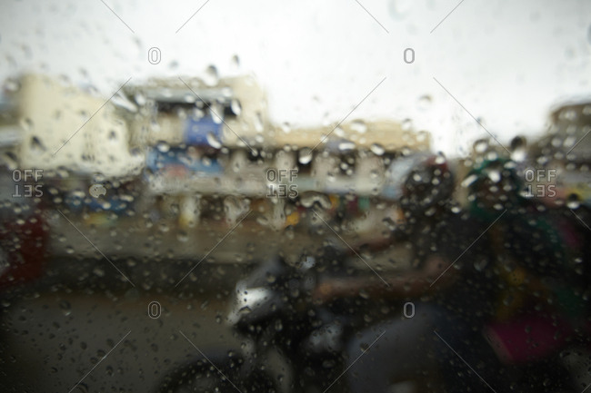 View of motorbike through window covered in rain droplets, Bangalore, India