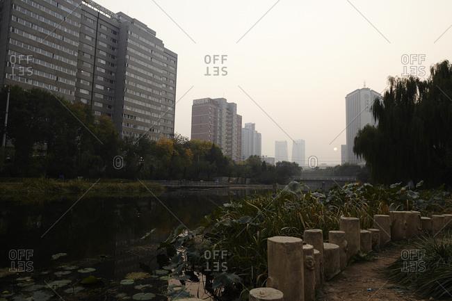 Beijing, China - October 7, 2014: Hazy sunset over river in Beijing, China