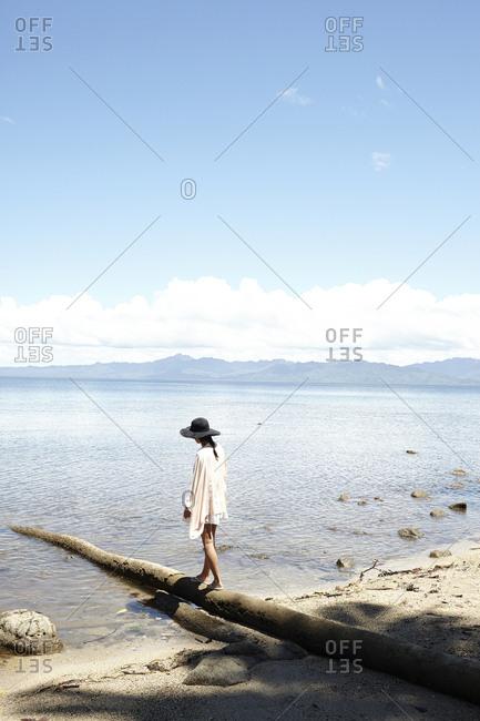 Savusavu, Fiji - February 17, 2015: Woman walking on a fallen tree on the beach at Savusavu Bay, Savusavu, Fiji