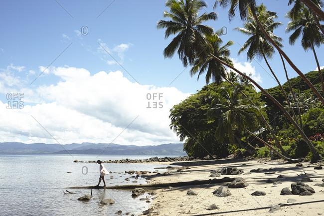 Savusavu, Fiji - February 17, 2015: Woman walking on a fallen tree at Savusavu Bay, Savusavu, Fiji