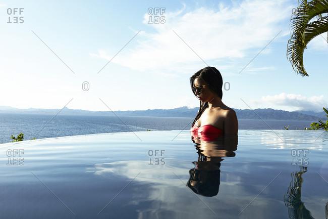 Savusavu, Fiji - February 17, 2015: Young woman in bikini in a, infinity pool, Savusavu Bay, Savusavu, Fiji