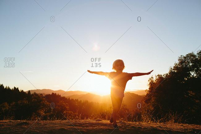 Boy backlit by sun in rural hills