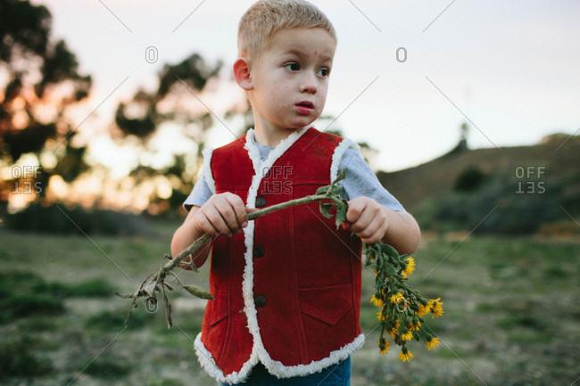 Boy in vest holding wildflowers