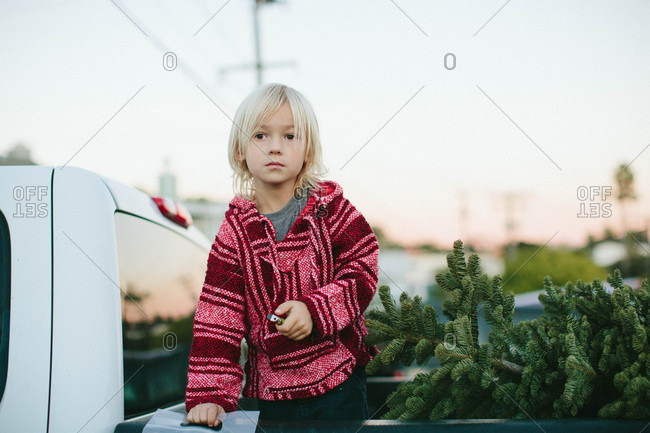 Boy in back of truck with Christmas tree