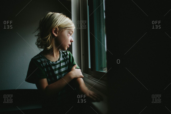 Boy with black eye gazing out window