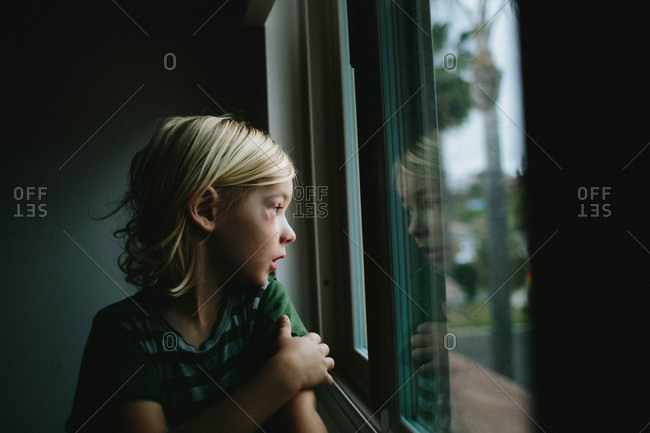 Boy with black eye looking out window