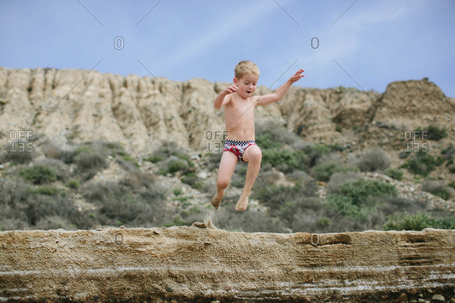 Boy leaping from a rock formation