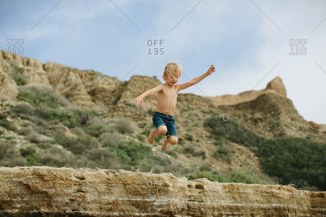 Boy jumping from a rock formation