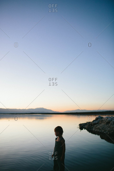Boy standing by lake in evening