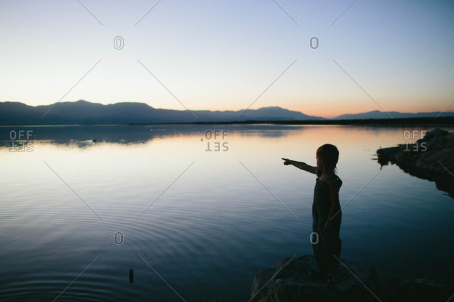 Boy pointing by lake at dusk