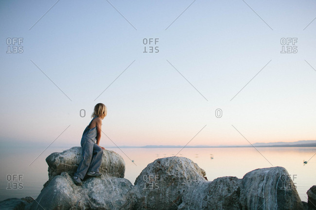 Boy on lake boulders at dusk