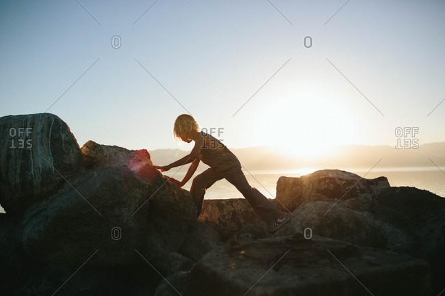 Boy backlit by sun on rocks