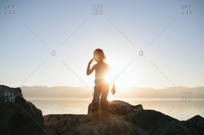 Boy on rocks backlit by sun