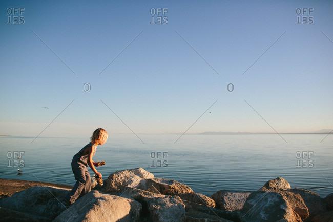 Boy climbing boulders by lake