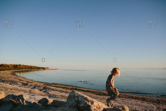 Boy exploring beach by lake