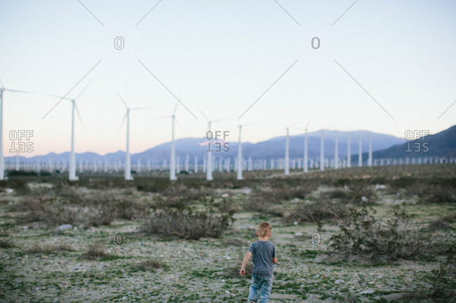 Boy standing by rural wind farm