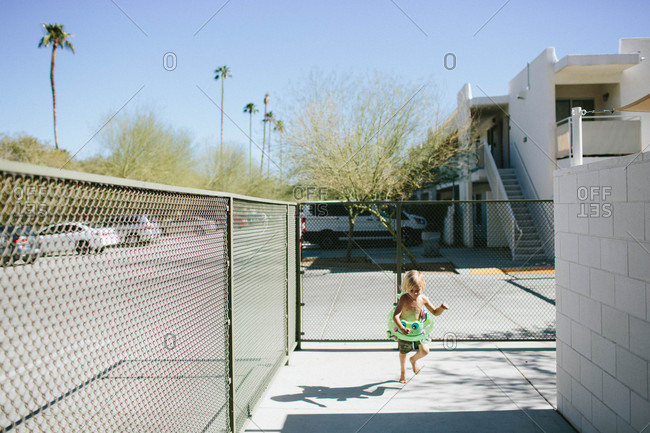 Boy running wearing swimming ring