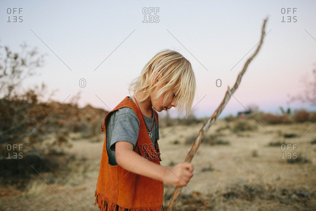 Boy with a stick in desert setting