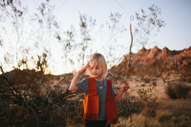 Boy with stick in desert setting