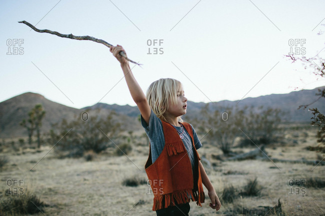 Boy holding a stick in desert setting