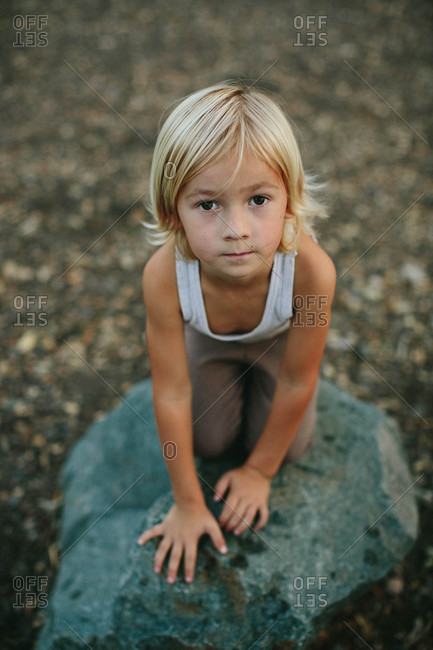 Boy kneeling on a rock outside