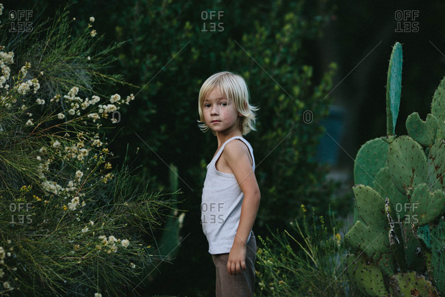 Boy in tank top by cactus plants
