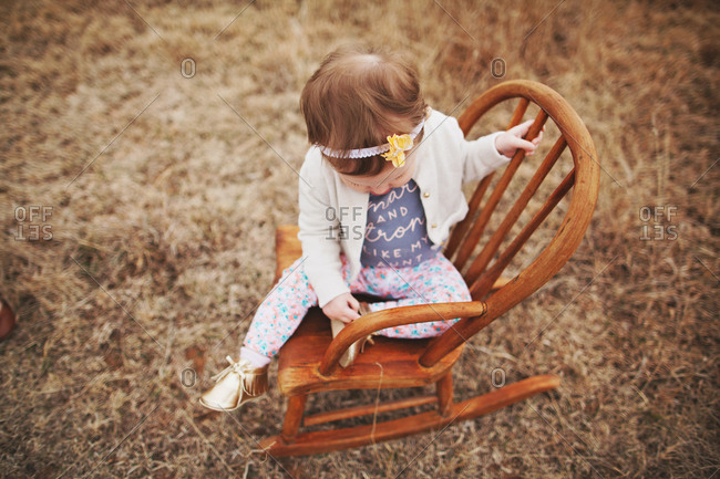 Girl on a rocking chair outside