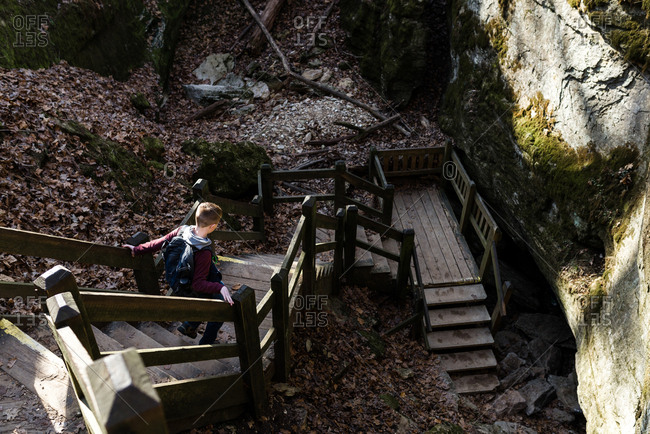 Boy walking on a wooden staircase in the woods