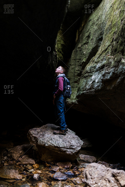 Boy standing on a rock at the entrance to a cave