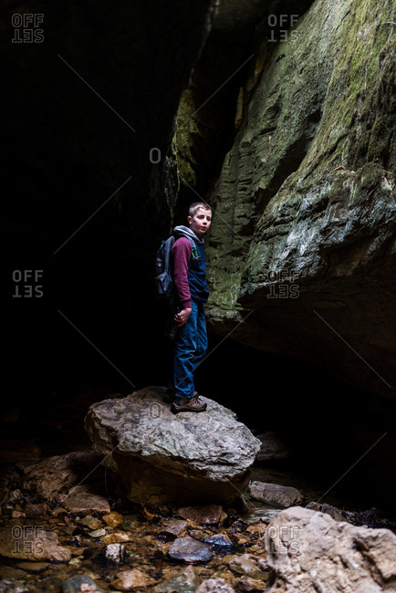 Boy standing on a rock in a cave in the wilderness
