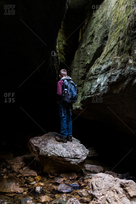 Boy exploring a rocky cave in the wilderness