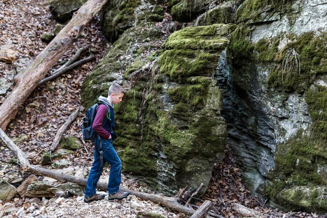 Boy hiking near mossy rocks in the woods