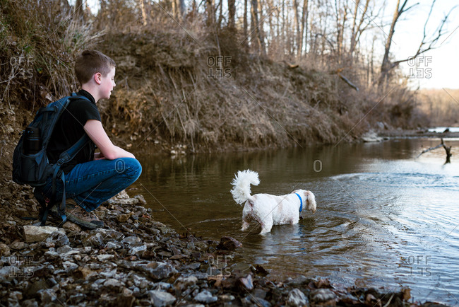 Boy watching his dog wade in a shallow river