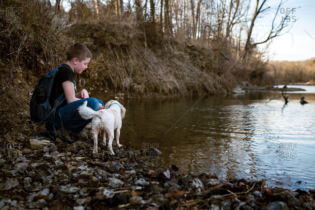 Boy crouching by a river with his dog