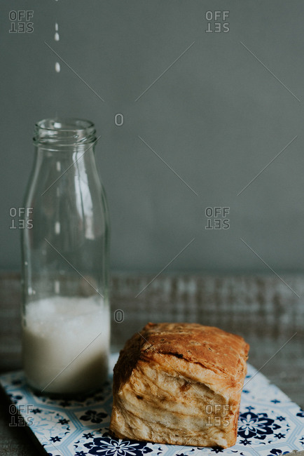 Flaky pastry and glass jar of milk