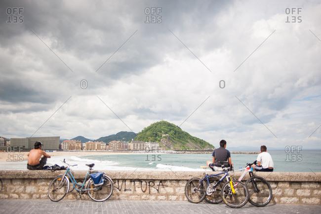 Donostia / San Sebastian, Spain - July 22, 2015: Young men with bikes sitting on wall overlooking Playa de Gros