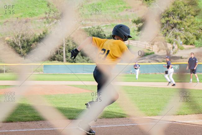 Boy running between bases at a baseball game