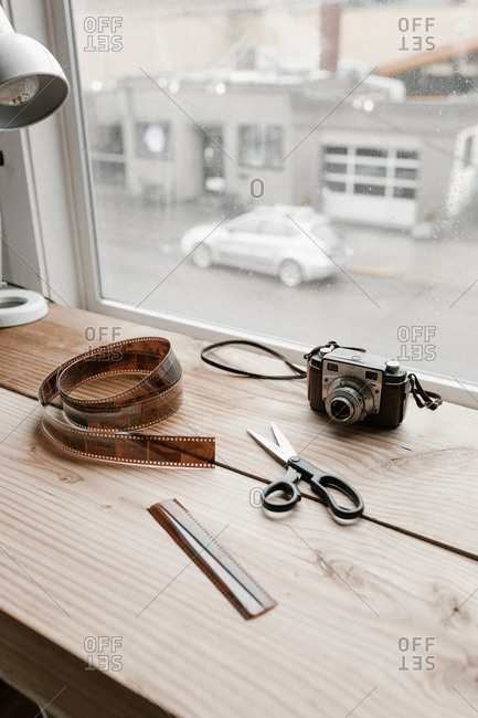 Vintage camera, scissors and film on a work surface at a window