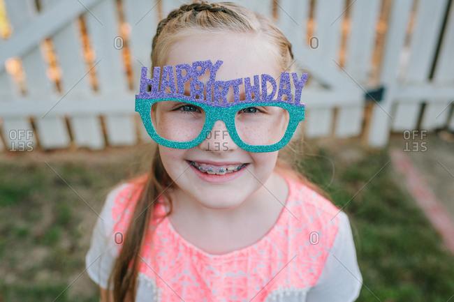 Little girl wearing Happy Birthday glasses