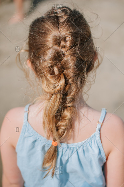 Rear view of blonde girl with a messy braid