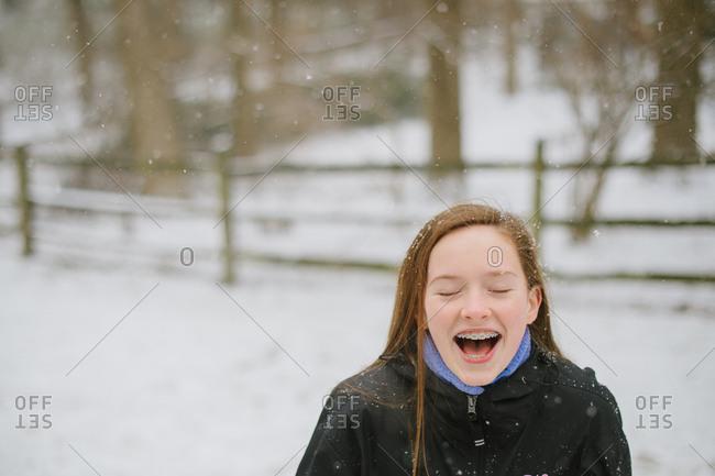Tween girl outside in the snowfall