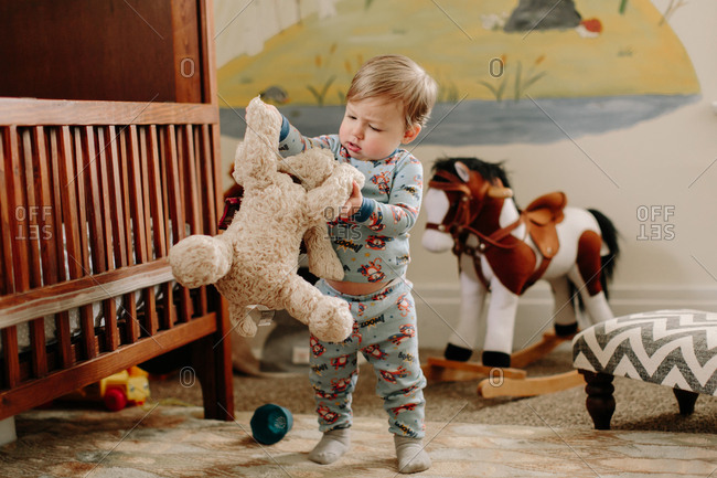 Toddler boy playing with stuffed animal in bedroom