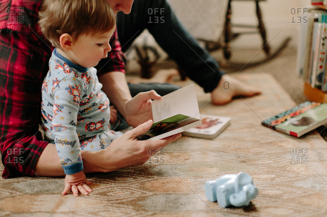 Man reading to toddler son in bedroom