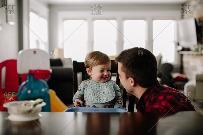 Toddler boy in booster seat smiles at father