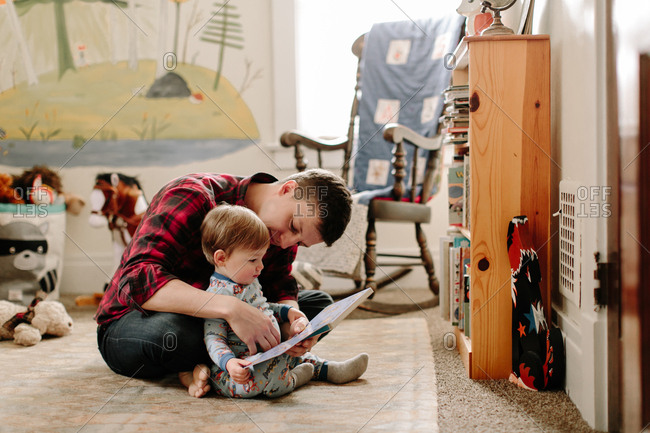Father reading to his toddler son in bedroom