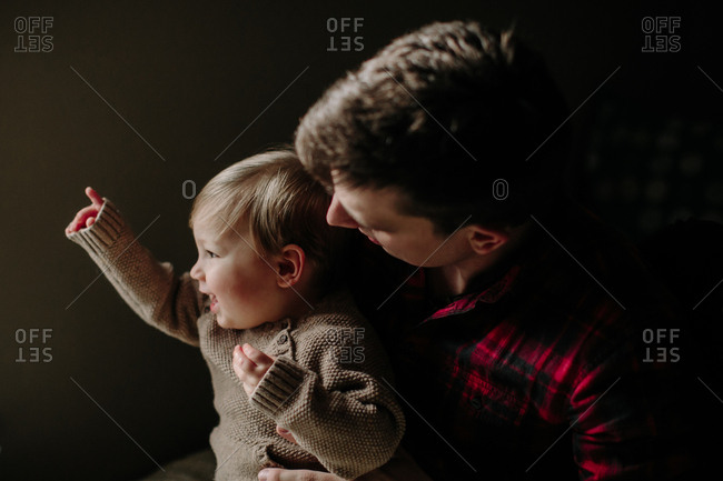 Father holding toddler son on his lap
