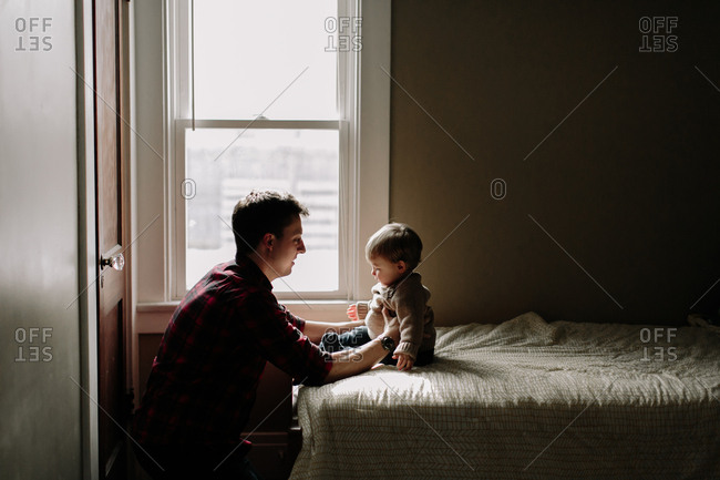 Father with toddler son on bed near window