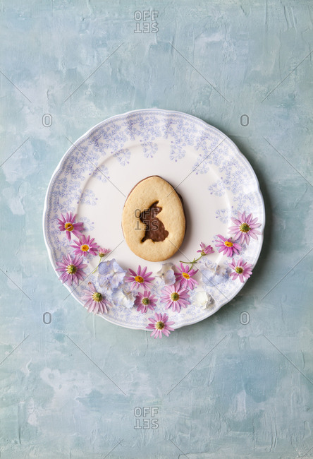 Cut out of an easter bunny on a chocolate cookie plated with wild flowers